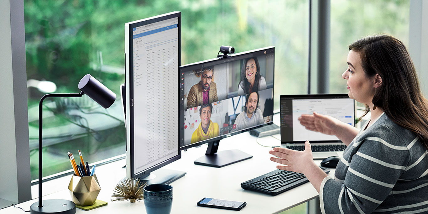 Working woman from home, in front of her two monitors, holds an online meeting with her partners via Microsoft Teams