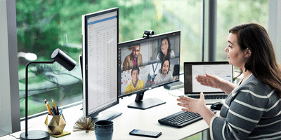 Α woman is working from home, in front of her two monitors, holds an online meeting with her partners via Microsoft Teams
